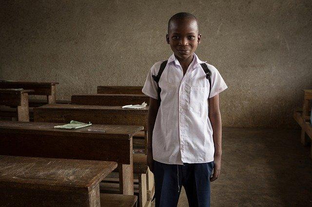 chlapec stojící u školní lavice